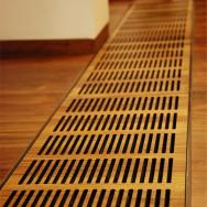 Detail masivní podlahy s mřížkou podlahového radiátoru